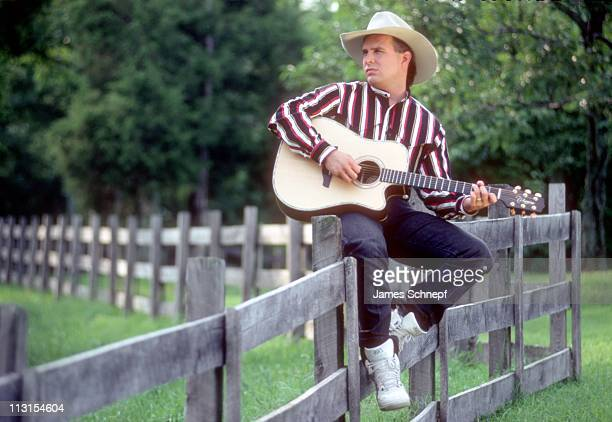 Country music star Garth Brooks poses for a portrait session on a fence wearing a cowboy hat and playing a Takamine acoustic guitar on August 15 1991...