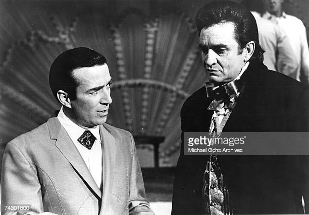 Country musicians Faron Young and Johnny Cash chat in circa 1965