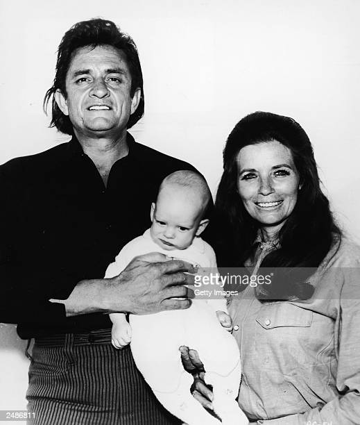 Country musicians Johnny Cash and his wife June Carter Cash hold their infant son John Carter Cash in a promotional portrait for the film 'A...