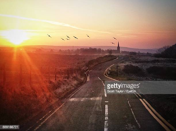 Country Road Amidst Field Against Sky During Sunrise