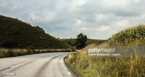 Country Road Amidst Grassy Field Against Cloudy Sky