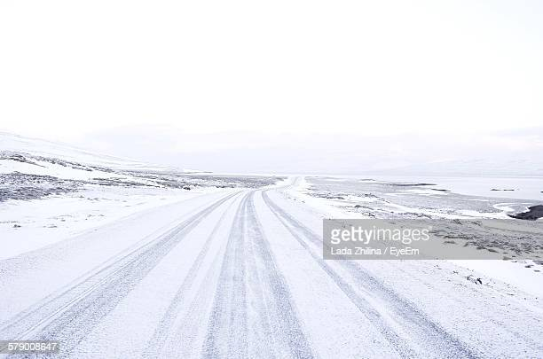 Country Road Amidst Snowcapped Landscape Against Sky