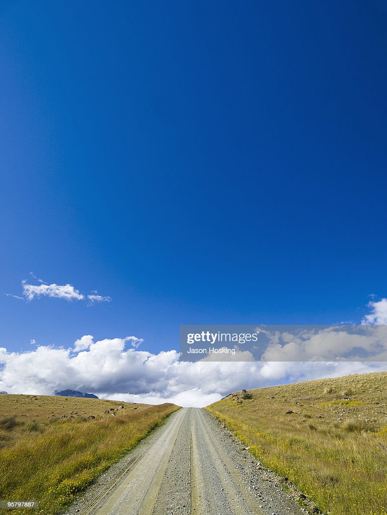Country road leading over hillside : Stock Photo