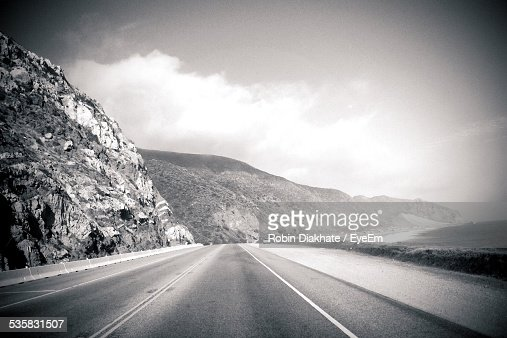 Country Road Leading Towards Mountains Against Sky