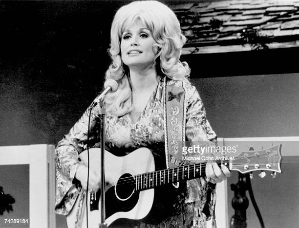 Country singer Dolly Parton performs onstage with an acoustic guitar in circa 1974