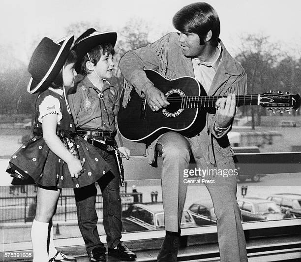 Country singer Glen Campbell playing the guitar for two young fans Renata Romoli and Francis Bradford wearing cowboys hats outside the Hilton Hotel...