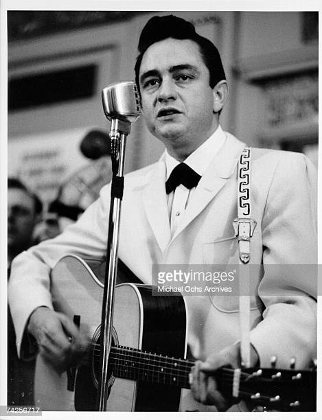 Country singer Johnny Cash performs onstage with an acoustic guitar in circa 1958