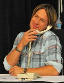 Country singer Keith Urban works the phone bank during the 'Music City Keep on Playin'' benefit concert at the Nashville Convention center on May 16...