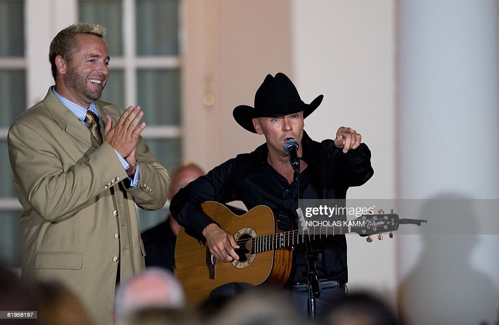 US country singer Kenny Chesney (R) jokes with Baltimore Orioles baseball player Kevin Millar (L) during a performance in the Rose Garden at the White House following a dinner in honor of Major League Baseball on July 16, 2008. AFP PHOTO / Nicholas KAMM