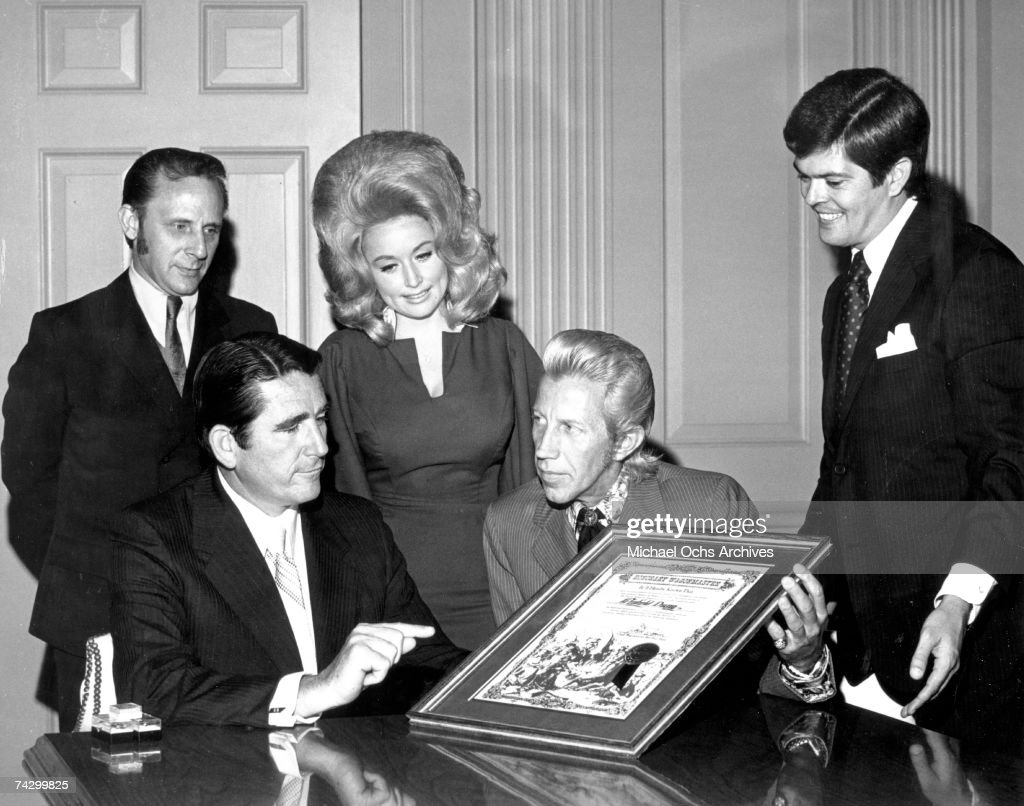 Country singer Porter Wagoner flanked by Dolly Parton and two other men presents a man with an 'Honorary Wagonmaster' plaque in circa 1968.