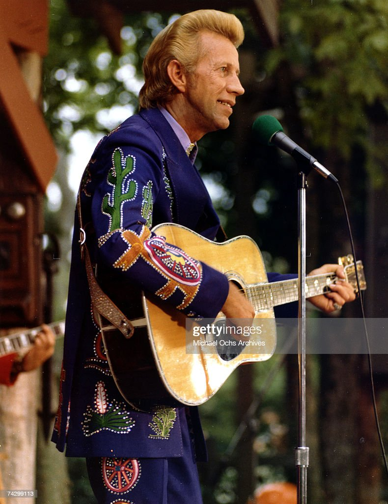 Country singer Porter Wagoner performs onstage with an acoustic guitar in circa 1973. Mr. Wagoner is wearing a Nudie Suit designed by Nudie Cohn of Nudie's Rodeo Tailors.