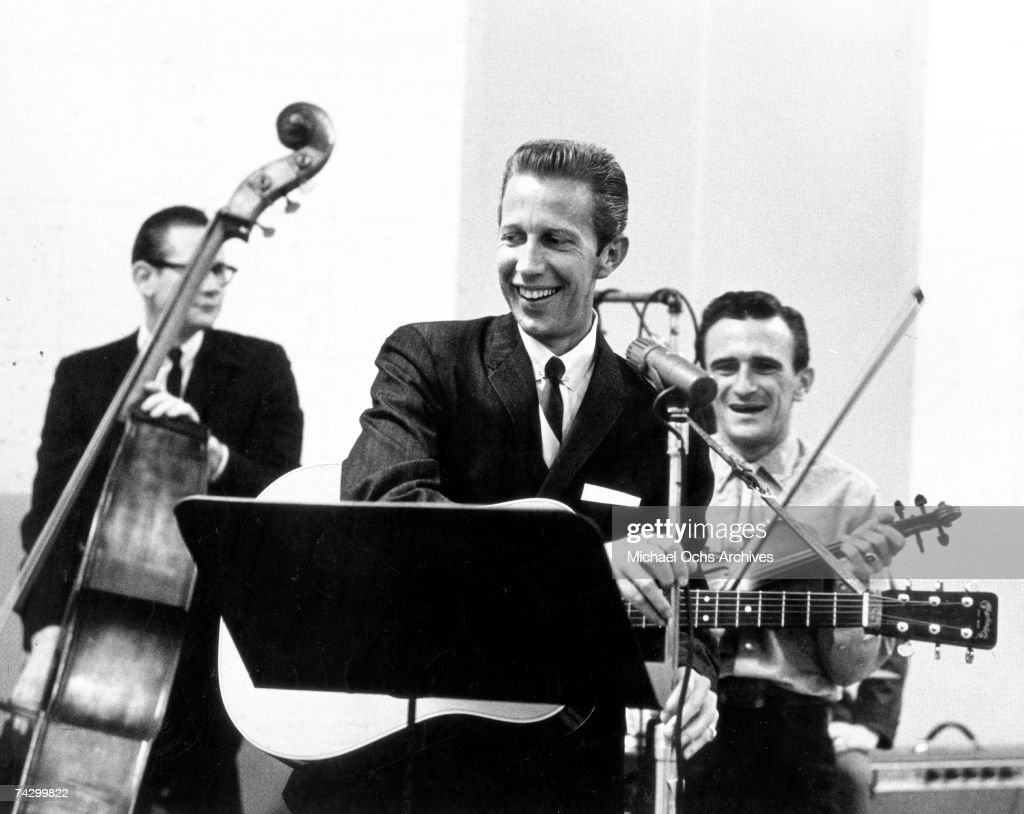 Country singer Porter Wagoner records vocals and acoustic guitar in the studio with his upright bass player and fiddle player in circa 1963.