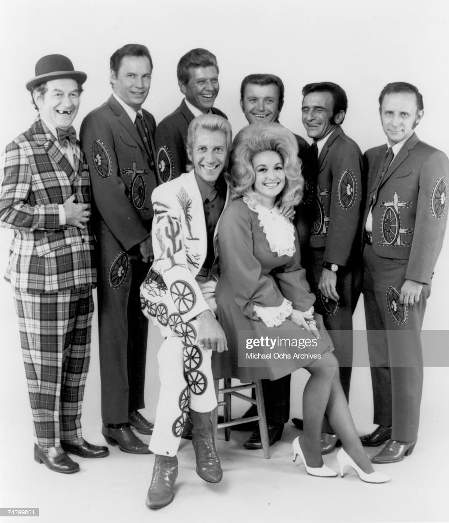 Country singers and collaborators Porter Wagoner and Dolly Parton pose for a portrait with their back up band, 'The Wagonmasters', in circa 1968. Mr. Wagoner is wearing a Nudie Suit designed by Nudie Cohn of Nudie's Rodeo Tailors.