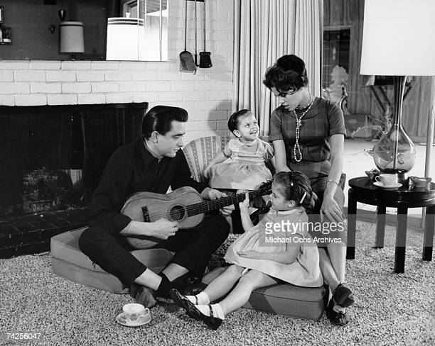 Country singer/songwriter Johnny Cash holds a guitar as his wife Vivian Liberto and daughters Rosanne Cash and Kathy Cash look on in 1957
