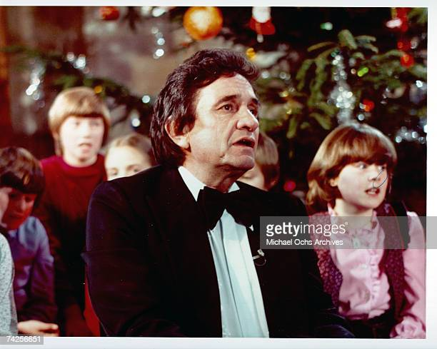 Country singer/songwriter Johnny Cash in front of a Christmas tree surrounded by children in circa 1975
