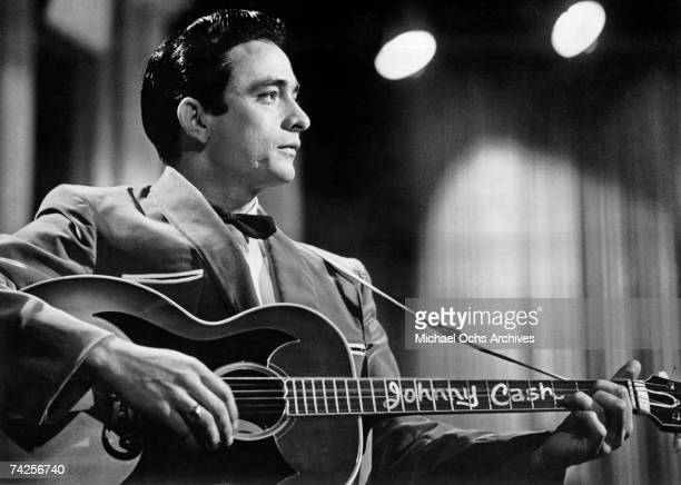 Country singer/songwriter Johnny Cash performs onstage with an acoustic guitar in 1957
