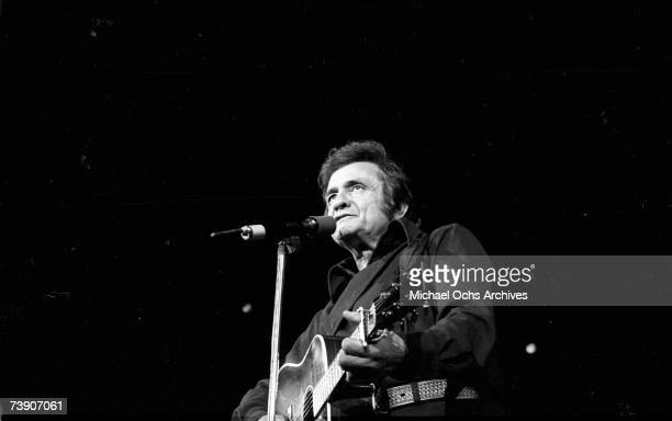Country singer/songwriter Johnny Cash plays acoustic guitar as he performs onstage at the Anaheim Convention Center on March 11 1978 in Anaheim...