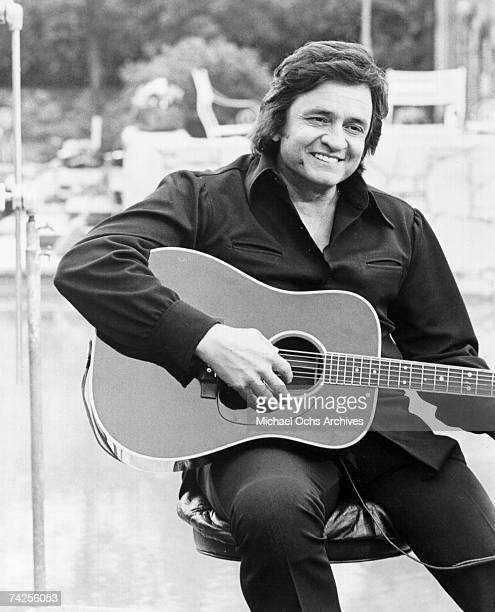 Country singer/songwriter Johnny Cash poses for a portrait holding an acoustic guitar in circa 1977