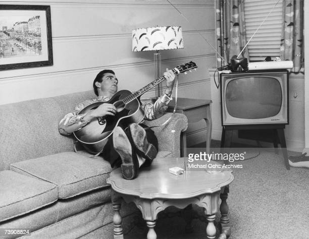 Country singer/songwriter Johnny Cash reclines on a couch while playing acoustic guitar in 1960 in Nashville Tennessee
