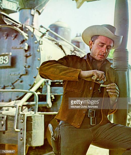 Country singer/songwriter Johnny Cash wears a gun in a holster and a cowboy hat as he gets his hands dirty in front of a train in circa 1965