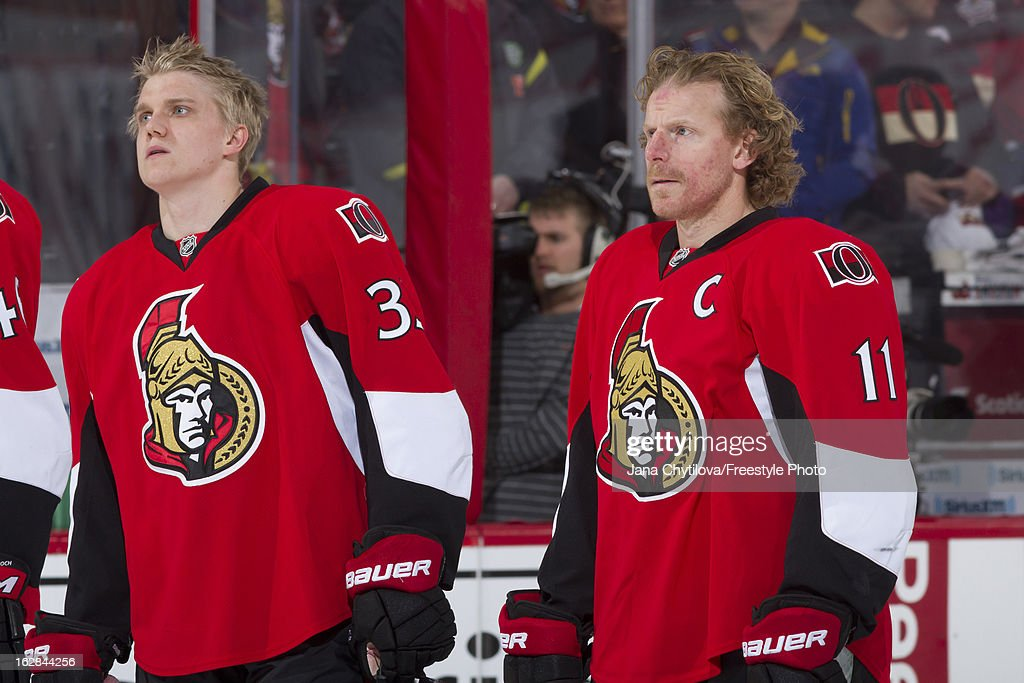 Countrymen and linemates Jakob Silfverberg #33 and Daniel Alfredsson #11 of the Ottawa Senators stand during the singing of the national anthems prior to an NHL game against the Montreal Canadiens, at Scotiabank Place on February 25, 2013 in Ottawa, Ontario, Canada.
