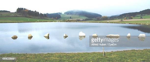 Countryside shot of stepping stones in lake against landscape