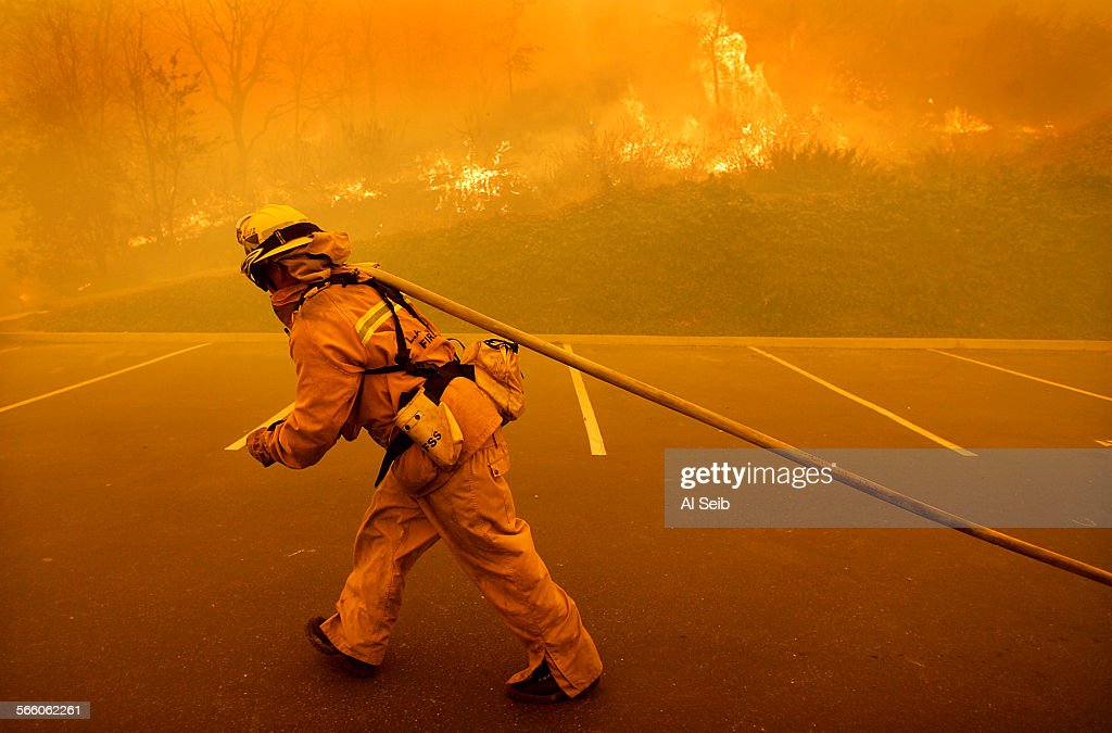 LA County Firefighter Ron Hughes with squad 89 drags hose to protect a commercial building along Agoura Road as a brush fire burns in the hills...