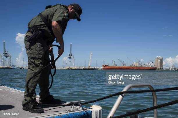 A county sheriff officer unties rope from a dock while preparing for departure at Port Canaveral in Cape Canaveral Florida US on Wednesday July 5...