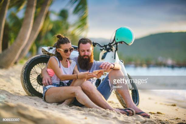 A couple - a bearded man and his handsome girlfriend - sitting on the beach leaned on motorbike, watching sunset at the sea