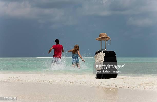 Couple abandoning luggage on beach