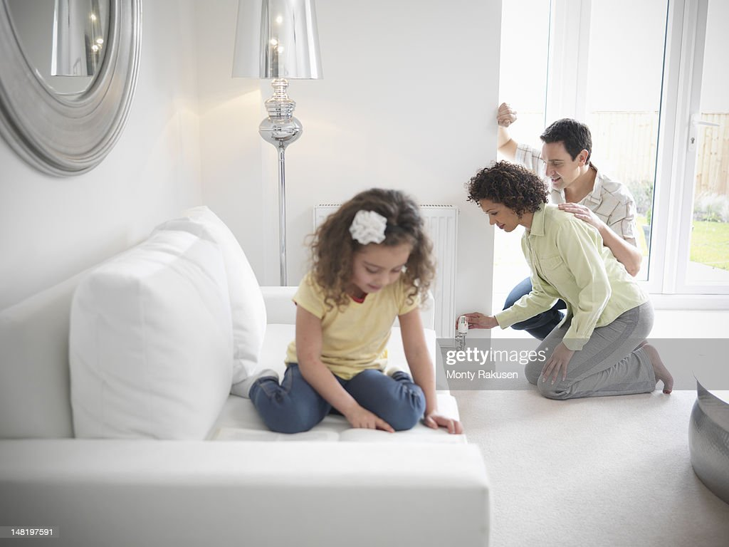 Couple adjusting radiator valve while daughter plays on sofa in living room