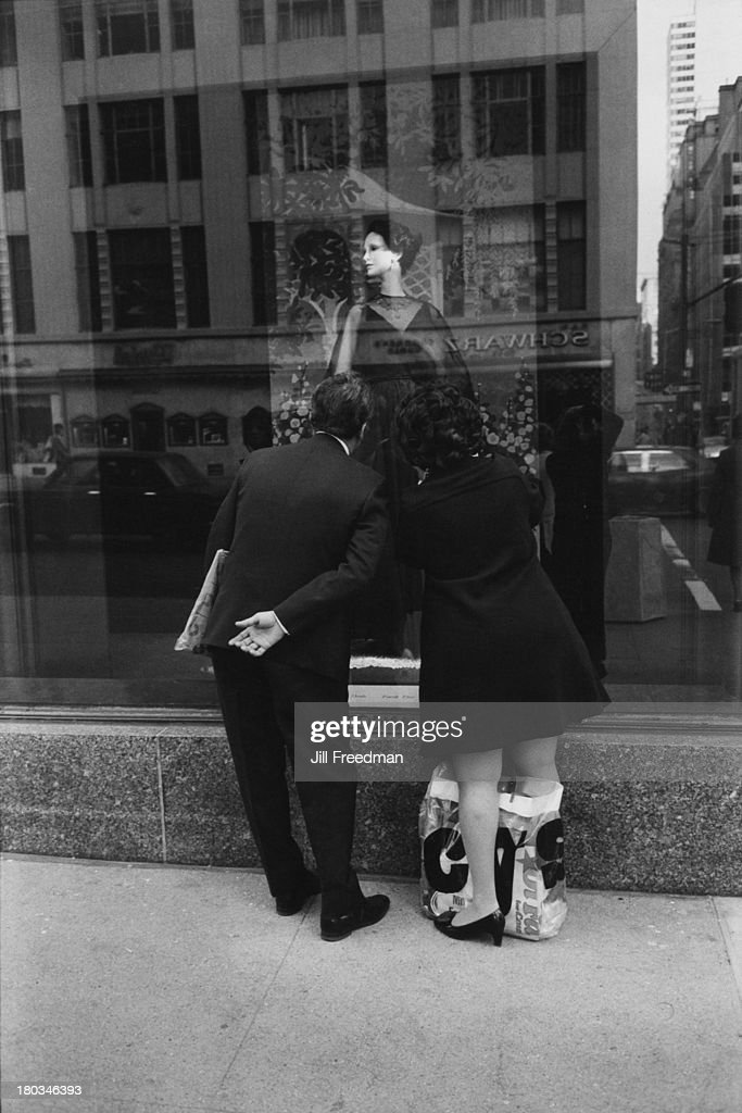 A couple admire a dress in the window of Bergdorf Goodman 5th Avenue New York City 1973