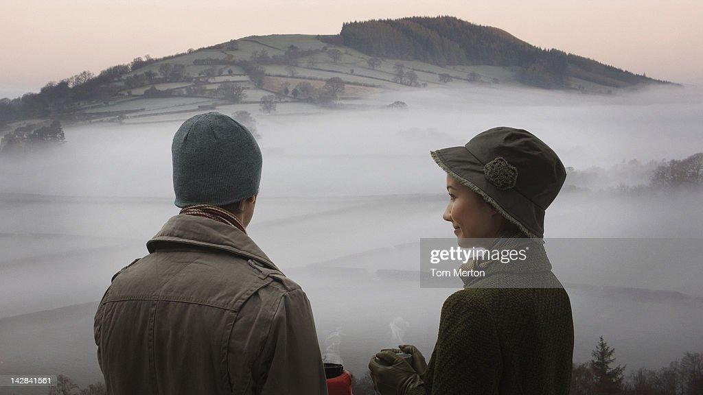 Couple admiring foggy landscape : Stock Photo