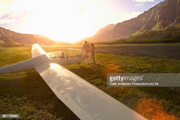 Couple admiring glider airplane on remote runway