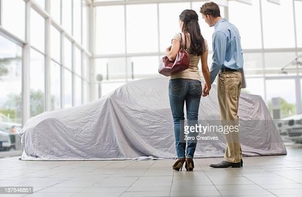Couple admiring new car under cloth