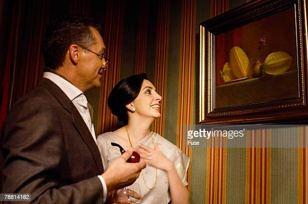 Couple Admiring Oil Painting on Wall
