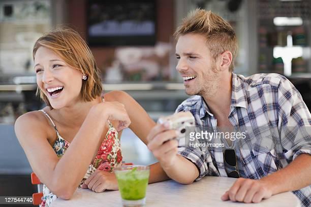Couple admiring photos at cafe