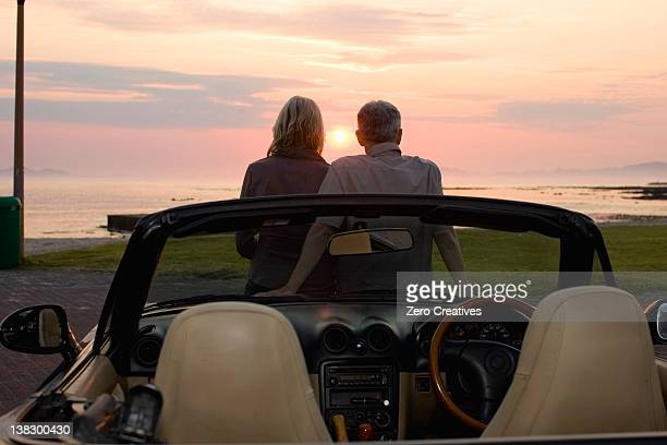 Couple admiring sunset in convertible