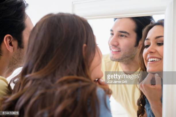Couple admiring themselves in mirror