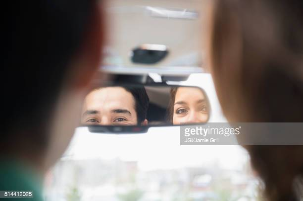 Couple admiring themselves in rearview mirror
