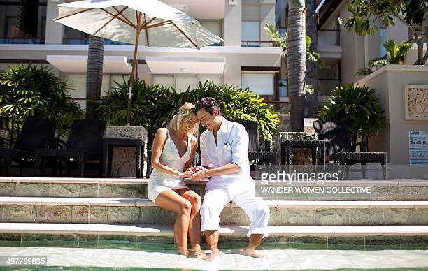 Couple admiring wedding ring by resort pool