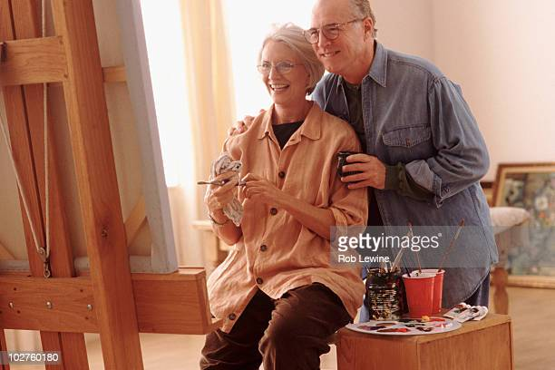 Couple admiring woman's painting