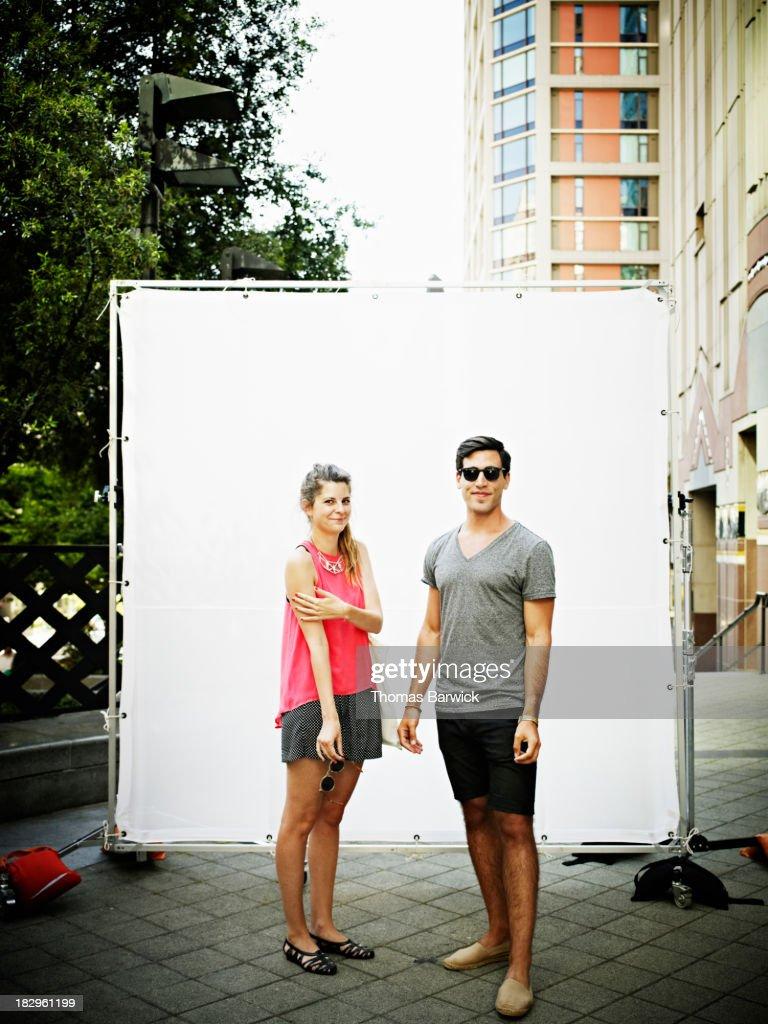 Couple against white background smiling
