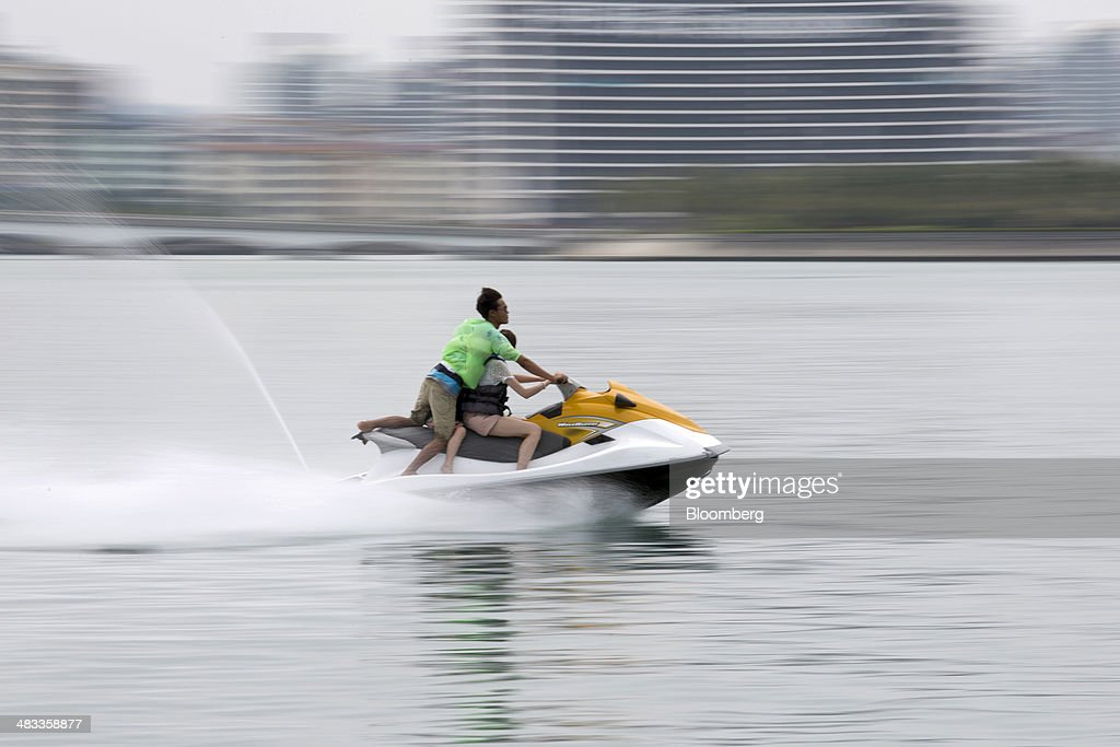 A couple and a child ride on a jet ski in the Sanya Bay district of Sanya, Hainan Province, China, on Monday, April 7, 2014. The yuan is poised to recover from declines that have made it Asia's worst-performing currency as China seeks to prevent an exodus of capital that would threaten economic growth, according to the most accurate forecasters. Photographer: Brent Lewin/Bloomberg via Getty Images