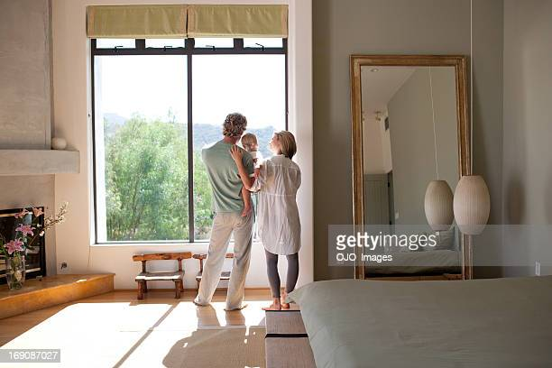 Couple and baby son looking out window