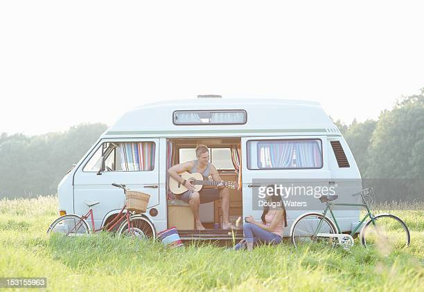 Couple and camper van in countryside.