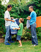 Couple and child hanging laundry