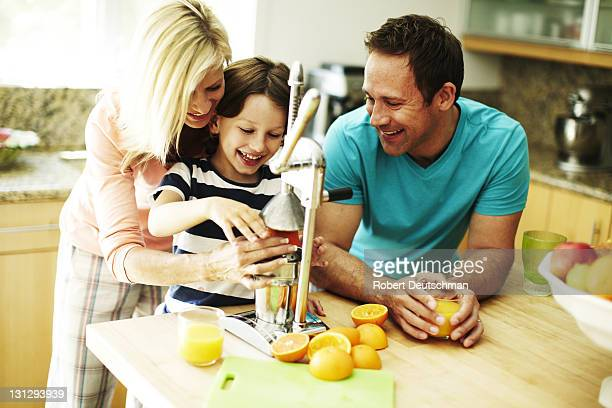 A couple and child squeezing oranges.