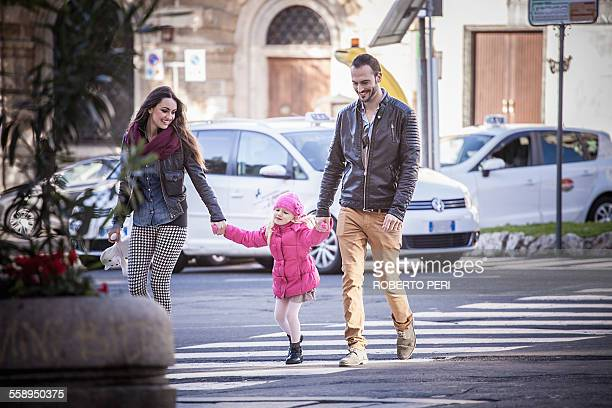 Couple and daughter holding hands on pelican crossing, Cagliari, Sardinia, Italy