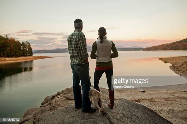 Couple and dog admiring remote lake
